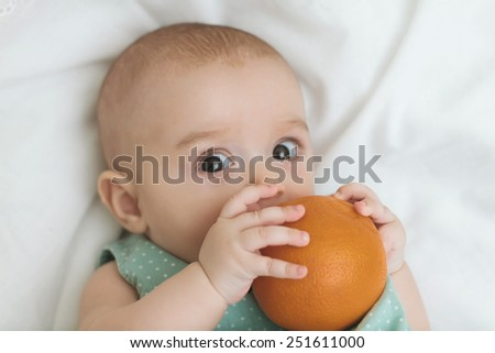 Adorable little baby girl with orange laughing, creeping & playing in the studio, on white background - stock photo