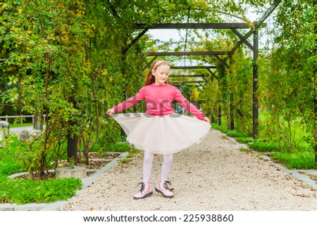 Adorable little girl spinning around in a beautiful park on a nice sunny day, wearing tutu skirt, boots and bright pink pullover - stock photo