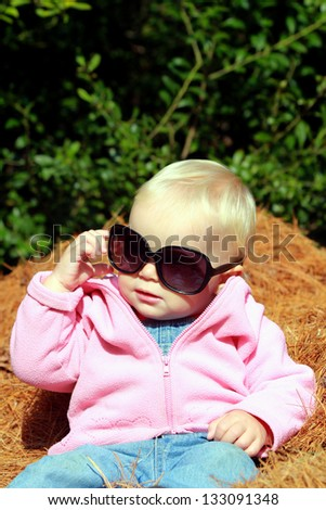 Adorable toddler girl in big sunglasses sitting on a hay - stock photo