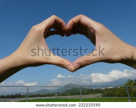 Adult hand making a heart shape against a beautiful blue sky in perspective - stock photo