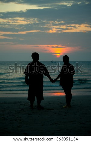 Adult male groom and female bride holding hands on beach at sunset. - stock photo