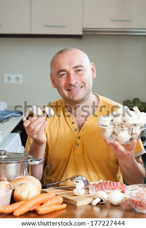 adult male  preparing soup in the kitchen - stock photo