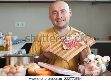 Adult man in  his kitchen preparing meat with mushrooms - stock photo