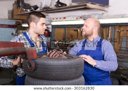 adult russian car mechanics in coveralls working at carshop - stock photo