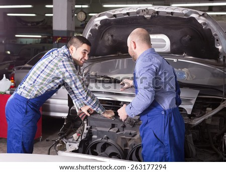 adult smiling car mechanics in coveralls working at carshop - stock photo