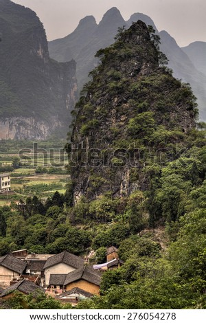 Aerial view of the karst hills around Guilin and the tiled roofs of stone farmhouses in a peasant village. Guangxi Zhuang autonomous region , southern China, Yangshuo, Guangxi.