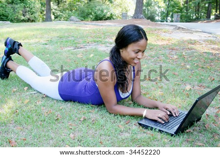 African american woman outside in the grass working on a computer - stock photo