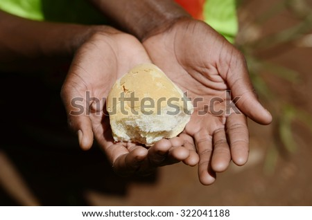 African Black Girl Holding Bread Malnutrition Hunger Stunted Symbol. Black African girl holding bread as a malnutrition symbol. Stop stunting, hungry children and water scarcity in the world!  - stock photo
