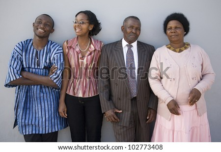 4 African people standing together against a wall. The younger ones look happy, the older ones serious. - stock photo