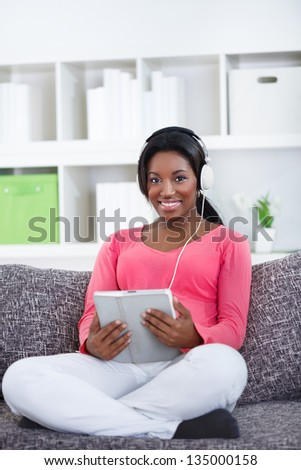 African woman with  digital tablet listen  music - stock photo