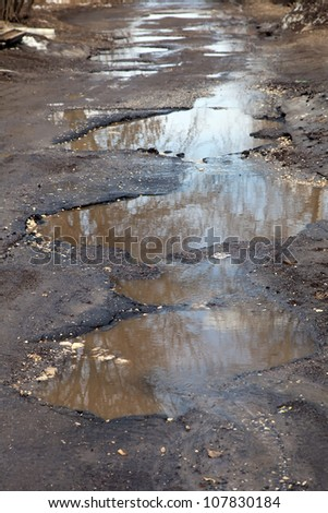 after winter a tarmac road has a large, deep, water filled potholes - stock photo