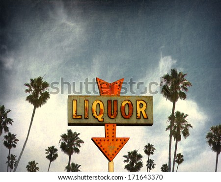 aged and worn vintage liquor neon sign with palm trees                               - stock photo