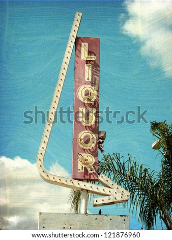 aged and worn vintage photo liquor sign with arrow - stock photo