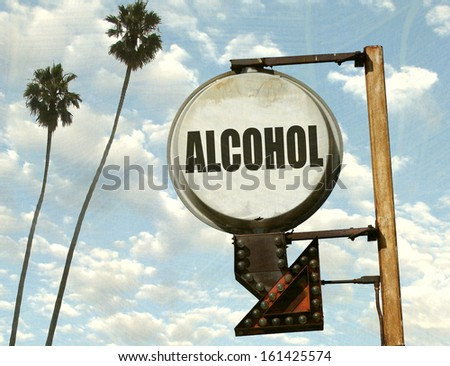 aged and worn vintage photo of alcohol sign with arrow and palm trees                               - stock photo