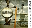 aged and worn vintage photo of beach sign with lifeguard tower and palm trees - stock photo