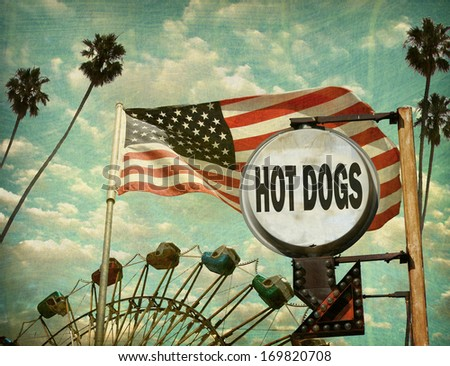 aged and worn vintage photo of hot dogs sign at amusement park with ferris wheel                              - stock photo