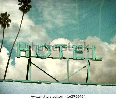 aged and worn vintage photo of hotel sign and palm trees                               - stock photo