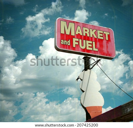 aged and worn vintage photo of  market and fuel sign with giant ice cream cone                             - stock photo