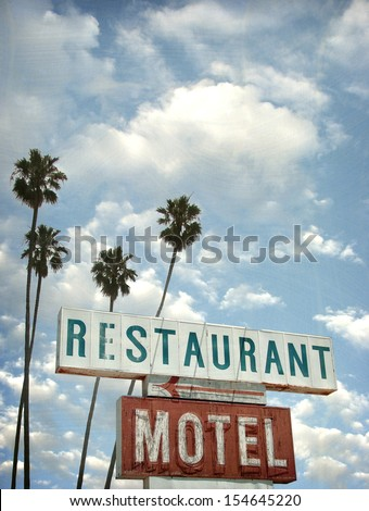 aged and worn vintage photo of motel and restaurant neon sign with palm trees                              - stock photo