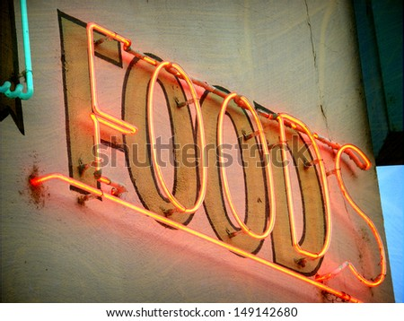 aged and worn vintage photo of neon food sign                               - stock photo