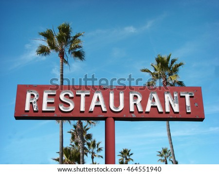 aged and worn vintage photo of neon restaurant sign with palm trees