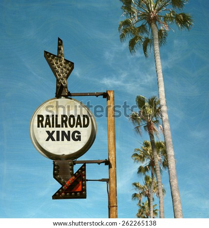 aged and worn vintage photo of railroad crossing sign with palm trees                              - stock photo