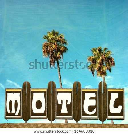 aged and worn vintage photo of retro motel sign and palm trees                               - stock photo