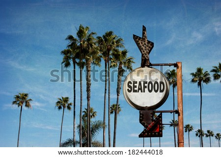 aged and worn vintage photo of  seafood sign with palm trees