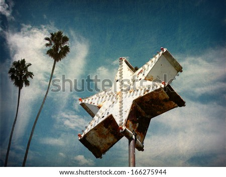 aged and worn vintage star neon sign with palm trees                               - stock photo