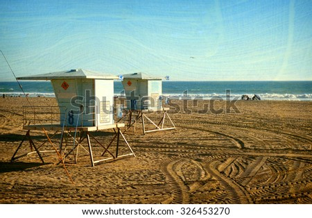aged vintage photo of lifeguard towers on beach                                   - stock photo