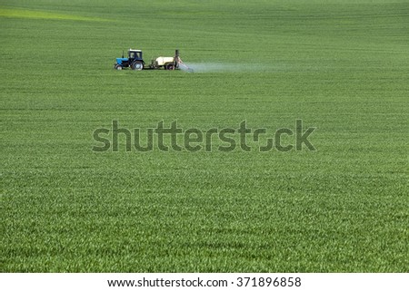 agricultural field where the green grass is treated with pesticides - stock photo