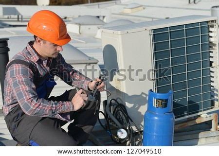 Air Conditioning Repair, young repairman on the roof fixing air conditioning system. Model is actual electrician. - stock photo