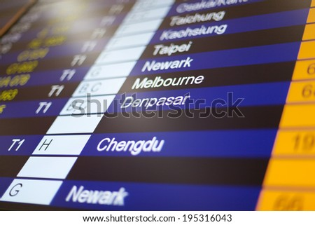 Airport arrival board in airport terminal. Travel concept. Denpasar in focus.