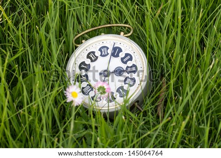 alarm clock outdoors sitting in grass on the morning of a bright sunny day. - stock photo