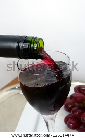 alcohol beverage drink being served at fine dining . red wine pouring from a bottle into a glass. - stock photo