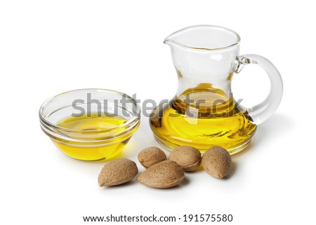 Almond oil and almonds on white background - stock photo