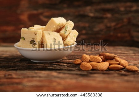 Almonds  served with flaky Indian dessert - Soan Halwa, - stock photo