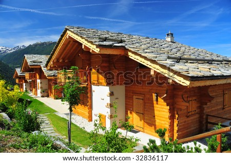 3 alpine chalets in the sunshine, with mountains in the background. With traditional rectangular section wood walls and stone roofs with snow protection - stock photo