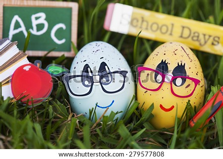 American education concept: ?? funny eggs with school objects on green grass   - stock photo