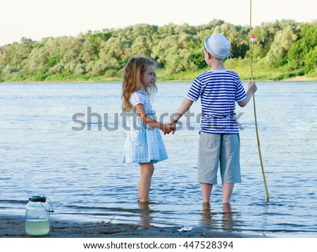 amusing boy and girl on the river summer day.toned - stock photo