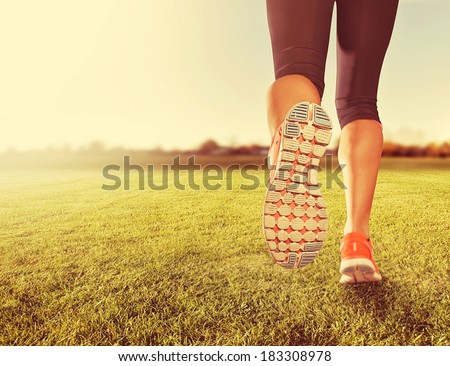 an athletic pair of legs on grass during sunrise or sunset - done with a soft vintage instagram  like filter - stock photo