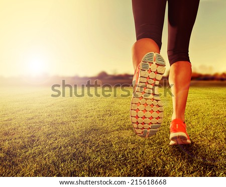an athletic pair of legs on grass during sunrise or sunset - done with a soft vintage instagram like filter