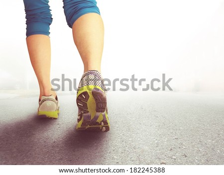 an athletic pair of legs on pavement during sunrise or sunset - healthy lifestyle concept  - stock photo