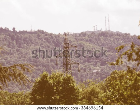 An electric power high voltage transmission line - selective focus on mast, with tv radio and mobile antenna aerial on background hill vintage - stock photo
