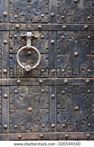 Ancient iron door handle on iron medieval door in Gdansk, Poland. - stock photo
