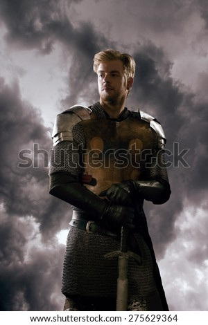 Ancient knight in metal armor with sword standing on a cloudy background - stock photo