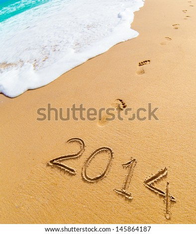 2014 and footprints on sand beach