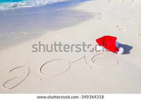 2016 and Merry Christmas written on beach white sand with red Santa hat - stock photo