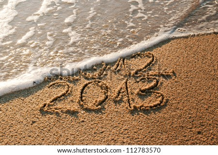 2012 and New year 2013 coming - waves erase year 2012 on the sandy beach - stock photo