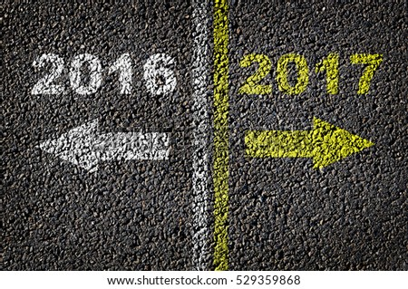 2016 and 2017 written on asphalt background in opposition direction